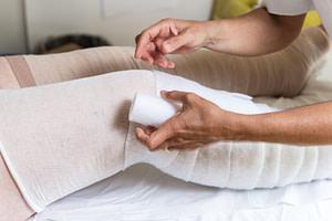 MLD therapist applying multi-layered compression bandaging